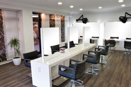Hairstyle Dogan mit weiß glänzenden robusten Oberflächen und dunklen Bezügen ergeben in diesem Salon ein weitläufiges Raumgefüge.