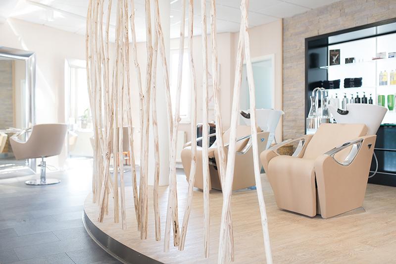 Moderner Friseursalon. Baumstämme als Raumteiler.