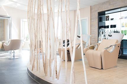 Friseuralon Haarmonie Simone Haas mit einem kontrastreichen Materialmix aus Holz, Edelstahl und Stein.Ein separater, durch hohe Baumstämme abgetrennter Herrenbereich und ein eigener Zweithaar-Studioraum runden das Angebot ab.