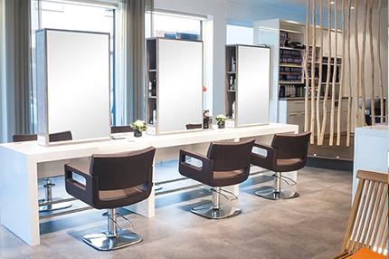Friseursalon Schneider mit Loft-ähnlichem Ambiente. Die Kombination aus direkter und indirekter Beleuchtung, die rand- und nahtlos in die Decke eingebaut wurde, verleiht dem Salon ein einzigartiges Flair